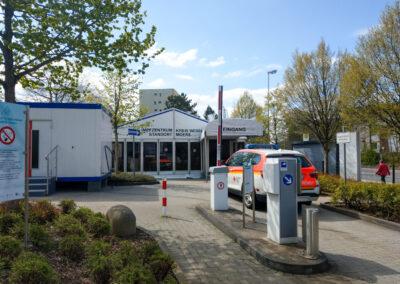 Impfzentrum Moers, Überdachter Eingang, vor dem Eingang steht ein Rettungsdienstwagen