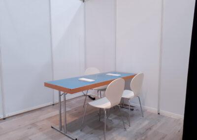 Trennwände aus Systembauteilen, in dem Bereich steht ein Tisch mit Spuckschutz und 3 Stühlen
