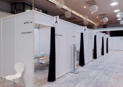 Trennwände aus Systembauteilen, Impfkabinen sind beschriftet und mit Vorhängen versehen. In den Kabinen steht ein Tisch, eine Liege, ein Stuhl, Auf dem Boden sind Richtungspfeile