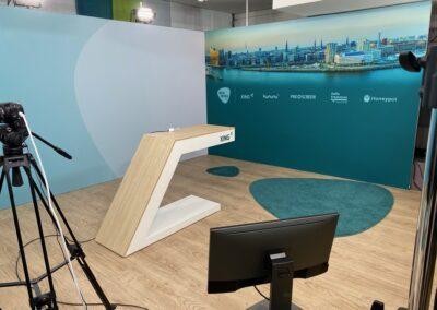 Octawall Wandbausystem mit TexPrint. In der Mitte des Messestandes steht ein individuelles Moderationspult. Ein Kamerastativ und ein Monitor stehen gegenüber des Pults