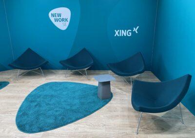 Interview Kulisse, Standard Messesystem OCTAwall mit blauen Wandgrafiken DEKOTEX Blockout, Stühle, Beistelltische ebenfalls blau, und blauer Hochfloorteppich in Logo-Emblem Form