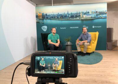 Interview Kulisse vor Skyline Grafik mit schwarzem und gelbem Ohrensessel auf Hochfloorteppich, Moderator mit Gast, Beistelltisch mit Wassergläsern und grüner Pflanze, Aufzeichnung