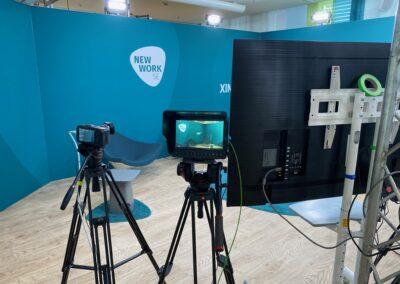 Aufzeichnung ZPEV, Kameratechnik, Standard Messesystem OCTAwall, mit Wandgrafiken DEKOTEX Blockout mit weißen Logos, blaue Stühle und Beistelltische, blauer Hochfloorteppich