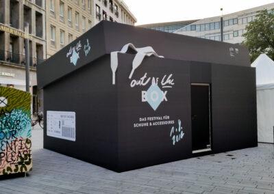 Großer Doppelcontainer als Schuhkarton mit Bühnenmolton verkleidet, der Karton ist mit Schrift beklebt. Auf dem Deckel liegen weiße Schnürsenkel aus Kunststoff