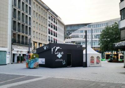 Großer Doppelcontainer als Schuhkarton mit Bühnenmolton verkleidet, der Karton/ Container hat eine Tür, man kann rein gehen. Auf dem Deckel liegen weiße Schnürsenkel aus Kunststoff