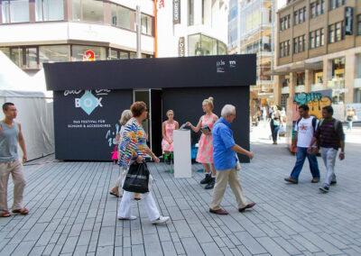 Großer Doppelcontainer als Schuhkarton mit Bühnenmolton verkleidet, der Karton/ Container hat eine Tür, man kann rein gehen. Promoterinnen stehen vor dem Container