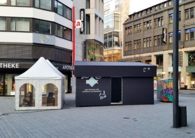 Großer Doppelcontainer als Schuhkarton mit Bühnenmolton verkleidet, der Karton/ Container hat eine Tür, man kann rein gehen. Neben dem Container steht ein Pagodenzelt