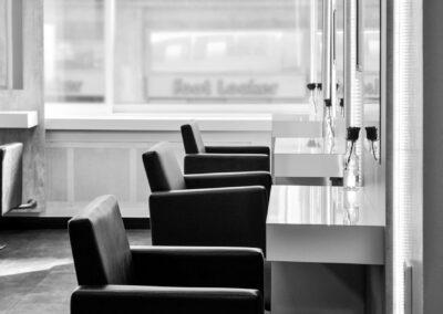 Friseursalon, Frisitertische, Frisierstühle, Spiegel, Rosen in Vase, modernes Ambiente, Hochglanzweiß, dunkelgrau, schlichter Stil, heller Raum