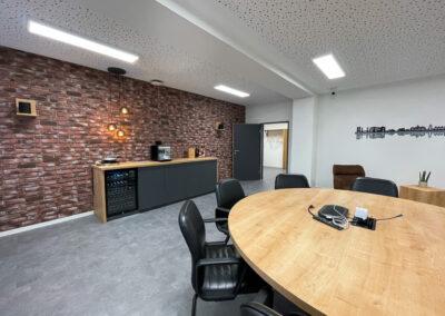 Runder Konferenztisch mit Holzoberfläche und Metallfuß, Anrichte aus Holz und KS grau inkl. Kühlschrank, Kaffeeanrichte, Skyline von Duisburg, Backsteinwand