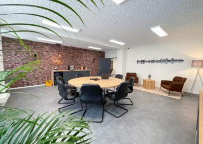 Besprechungsraum mit rundem Konferenztisch mit Holzoberfläche undLederstühlen, Wand in Ziegel-Optik, Folienschnitt mit Duisburger Skyline, Hängelampe, Anrichte mit Kühlschrank, Sitzecke