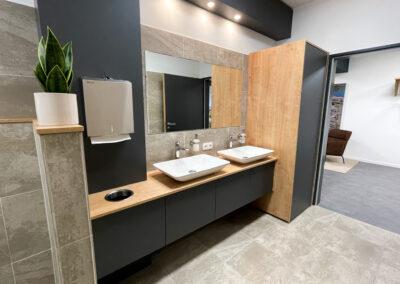 WC, weiße Porzellan Waschbecken, Unterschrank Waschbecken mit schwarzen Fronten und Eicheholzplatte, Spiegel, Wand- und Bodenfliesen in Betonoptik