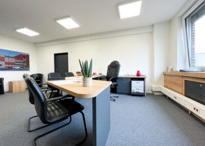 Büro mit großem Eiche Schreibtisch, schwarze Leder-Freischwinger für Kunden, schwarzer Leder-Drehstuhl, grauer Teppichboden, Heizungsverkleidung in Eicheoptik, Aktenschrank