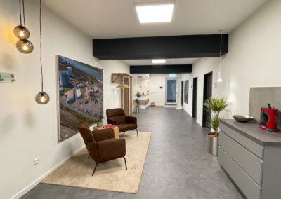 Wartebereich mit braunen Sessel und Coffeetable auf beigem Teppich, Bild in Printframe, Garderobe mit Holzleisten, Zimmerpalmen und Sideboard für Kaffeemaschine