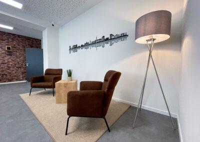 Besprechungsraum, Wand in Ziegel-Optik, Folienschnitt mit Duisburger Skyline, Hängelampe, Anrichte mit Kühlschrank, Sitzecke mit braunen Sesseln und Coffeetable, graue Stehlampe