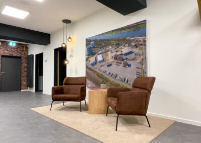 Sitzecke mit braunen Ledersesseln auf beigem Teppich, Coffeetable in Eiche-Optik, Print-Frame-Rahmen mit Bild, stylische Glashängelampe, grauer Fliesenboden in Beton-Optik