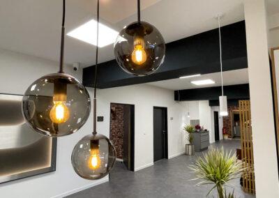 stylische Glashängelampe, grauer Fliesenboden in Beton-Optik, Zimmerpflanzen, Garderobe aus Echtholz-Holzleisten, graues Sideboard für Kaffeemaschine