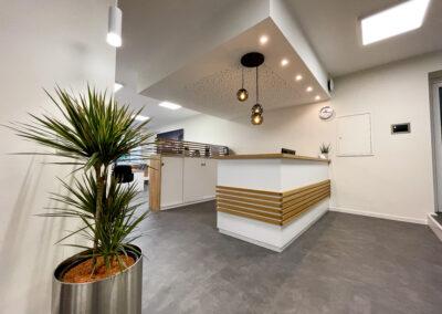 Weißer Empfangstresen mit Holz verkleidet, Sideboard mit Holzleisten als optischer Raumtrenner, grauer Vinylboden, Pflanze im Edelstahlübertopf