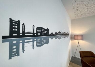 Besprechungsraum, Folienschnitt mit Duisburger Skyline, Hängelampe, Sitzecke mit braunem Sessel, graue Stehlampe