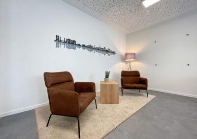Besprechungsraum, Folienschnitt mit Duisburger Skyline, Hängelampe, Sitzecke mit braunen Sesseln und Coffeetable auf beigem Teppich, graue Stehlampe