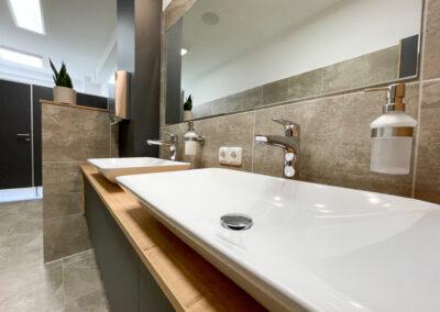 WC, weiße Porzellan Waschbecken, Unterschrank Waschbecken mit schwarzen Fronten und Eicheholzplatte, Spiegel, Wand- und Bodenfliesen in Betonoptik, WC Kabinen