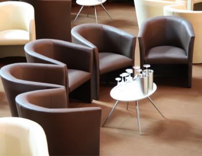 Fünf braune Ledersessel in U-Form angereiht vor einem kleinen ovalen Tisch
