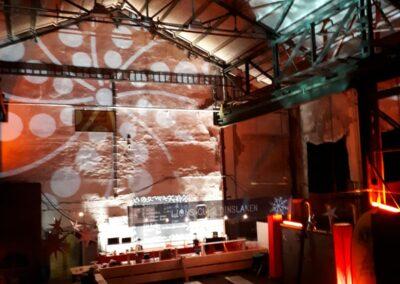Zeche Lohberg von innen. Eine bar mit Hintergrundbeleuchtung, davor stehen mehrere Bierzeltgarnituren.