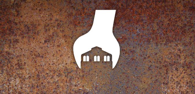 weißes Logo Zechenwerkstatt Lohberg auf rostig aussehenden Hintergrund