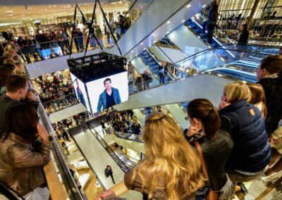 Modenschau Herrenmodenschau in einem Kaufhaus, Zuschauer stehen auf Rolltreppen, Zuschauer stehen auf allen Ebenen