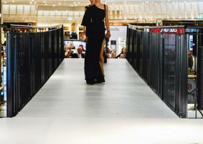 Damenmodenschau, zwei Models mit schwarzen Kleidern auf dem Laufsteg, davor stehen Zuschauer, die Bilder und Videos machen