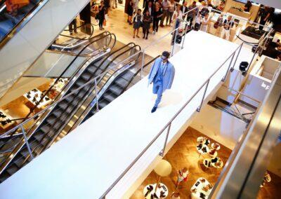 Modenschau Herrenmodenschau in einem Kaufhaus, Zuschauer stehen neben den Rolltreppen