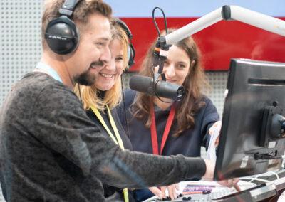 Studio, Aufnahmesituation mit drei Personen, zwei davon mit Headphones, Mischpult, Monitor und Mikrofon