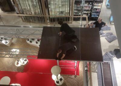 4-Punkt Traversen mit Podesten über der Galerie im Einkaufszentrum Breuninger in Düsseldorf, Monteure, die die Podeste befestigen