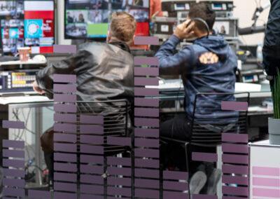 Studio, Glasscheibe mit lila Frequenzmotiv Grafik, dahinter Aufnahmesituation mit Technikern an Tisch mit Monitoren, Aufnahmeleitung