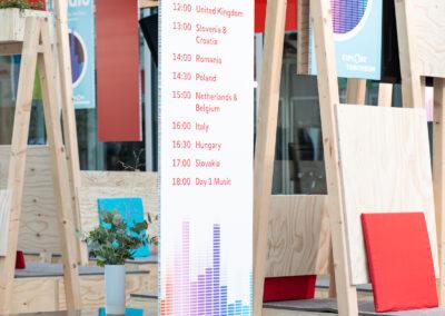 bedruckte Programm Grafiktafeln aus Leichtbauplatte mit ressourcenschonenden Kartonwabenkern, Loungebereich aus Seekiefer Sperrholz und Glas, Sitzoberfläche mit grauem Filz