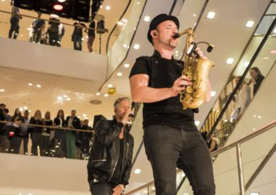 musikalisches Rahmenprogramm der Modenschau im Breuninger Kaufhaus in Düsseldorf: ein Saxophonspieler und ein Sänger, Publikum auf den verschiedenen Ebenen des Kaufhauses