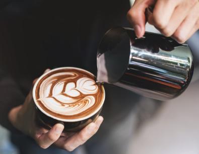 Nahaufnahme eines Barista, der Milch auf einen Kaffee gießt