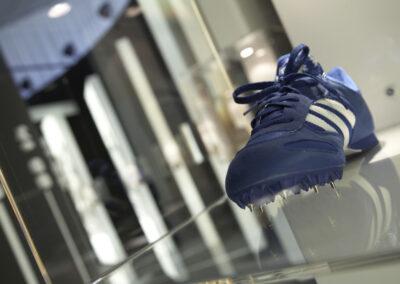 Showroom, blau-weißer adidas Sportschuh als Exponat in einer Glasvitrine