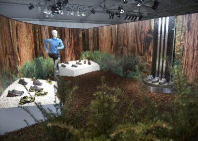 Showroom, inszenierte Waldkulisse mit Schaufensterpuppe in adidas Kleidung, Tische mit weißem Kies und Schuh-Exponaten, Alu Exponat-Stele, Digitaldruck: Waldmotiv, Kunstpflanzen