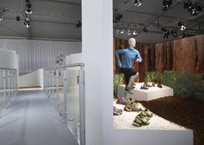 Galerie mit grauem Boden und Alugeländer mit Glasfronten, inszenierte Waldkulisse mit Schaufensterpuppe in adidas Kleidung, Tische mit weißem Kies und Schuhe,Digitaldruck:Waldmotiv