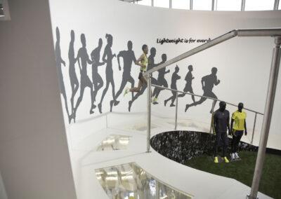 Kulissenbau, inszenierte Rennstrecke mit Geländer, Acrylboden mit Exonaten, Digitaldrucken mit Zuschauern und Läufern, Kunstrasen, Schaufensterpuppen in adidas Kleidung