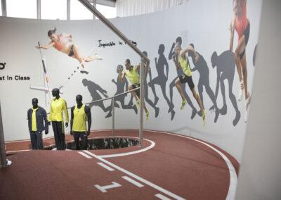 Kulissenbau, inszenierte Rennstrecke mit Geländer, Digitaldrucken mit Zuschauern und Sportlern, Kunstrasen, Schaufensterpuppen in adidas Kleidung auf Exponat-Siegertreppe