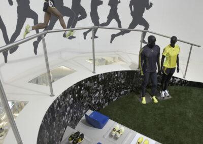 Tribüne in Beton-Optik mit Schuh-Exponaten und 3 blauen Schalensitzen, Digitaldrucke mit Läufern, vor Tribüne Schaufensterpuppe im adidas Outfit, Kunstrasen, Exponate in Vitrinen
