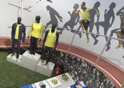 Tribüne in Beton-Optik mit Schuh-Exponaten und 3 blauen Schalensitzen, Rennstrecke, Digitaldrucke: Zuschauer und Sportler, vor Tribüne Schaufensterpuppe im adidas Outfit,Kunstrasen