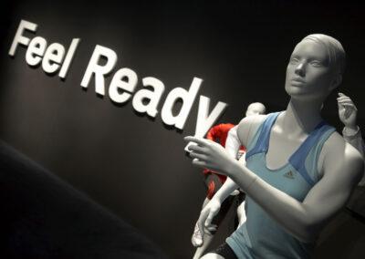 Showroom, graue sportliche Schaufensterpuppen mit adidas Kleidung, schwarze Rückwand mit weißem 3D Schriftzug