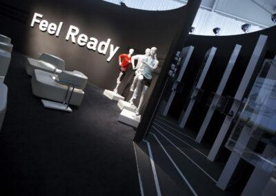Showroom, Lounge mit weißen Kunstledermöbeln, schwarze Wand mit weißen 3D Buchstaben, davor 3 Schaufensterpuppen im adidas-Outfit, Gang mit Exponaten in Acrylvitrinen