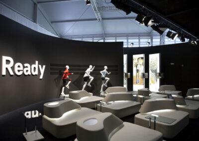 Showroom, Lounge mit weißen Kunstledermöbeln mit Tischen aus Glas, schwarze Wand mit weißen 3D Buchstaben und schwarzen adidas Streifen, davor 3 Schaufensterpuppen im adidas-Outfit