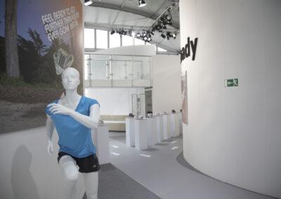 Showroom, sportliche Schaufensterpuppe mit adidas Kleidung, Exponate-Stelen mit Runningschuhen, Footprint-Folienplott auf dem Boden