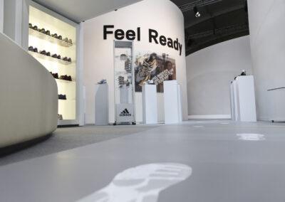 Showroom mit Sportschuh-Exponaten der adidas Produktlinien, ausgestellt auf Glas Vitrinen und Produktsäulen, Glasvitrine mit Sonnenbrillen, auf dem Boden Footprint-Folienschnitte