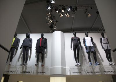 Showroom mit Exponaten der adidas Produktlinien, Schaufensterpuppen ausgestellt auf Acryl Regalen, die oben an der Wand montiert wurden