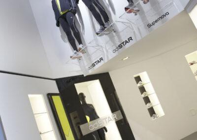 Showroom, Präsentation von Sportartikeln in beleuchteten Glasregalen und einer Glasvitrine, die Produktlinie entweder in 3D Buchstaben oder als Grafiken montiert